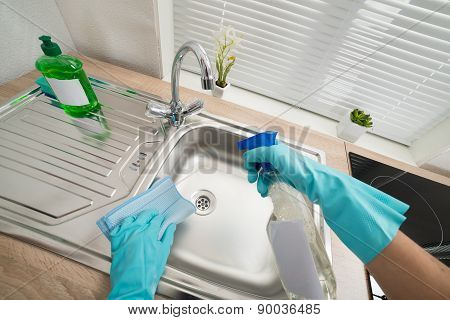 Person Hands In Blue Glove Cleaning Silver Kitchen Sink poster