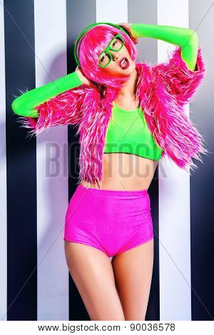 Trendy DJ girl in bright colorful clothes and headphones posing over black-and-white stripes. Party style. Fashion studio shot.