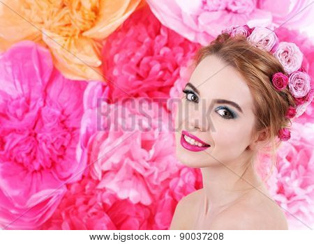 Portrait of young woman with flowers in hair on bright pink background
