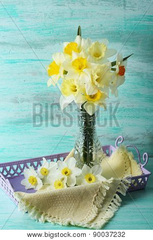 Fresh narcissus flowers on color wooden background