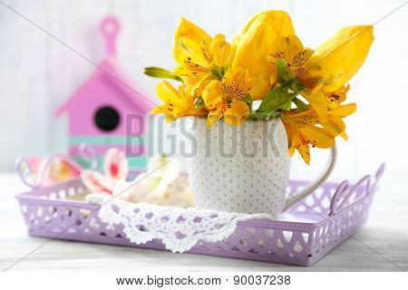 Beautiful flowers in cup, on wooden background