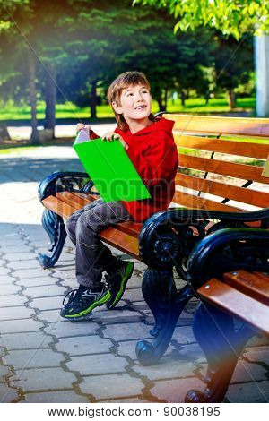 Happy boy sitting on the bench and reading a book. Summer day.