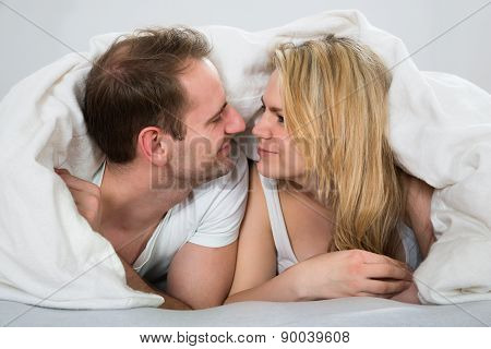 Couple Under Blanket Looking At Each Other
