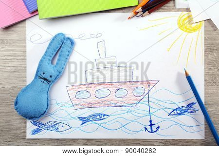 Kids drawing on white sheet of paper on wooden table, top view