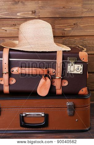 Stack of suitcases and hat on wooden background