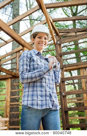 Portrait of happy female architect holding blueprint in incomplete wooden cabin at construction site