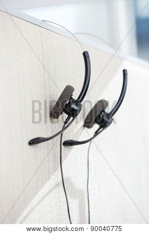 Headphones hanging on cubicle partition in office