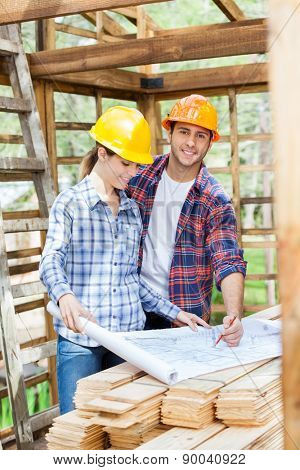 Portrait of happy architect examining blueprint with colleague at construction site