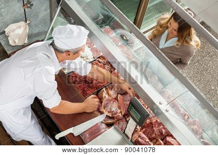 High angle view of butcher selling meat to customer at display cabinet in butchery