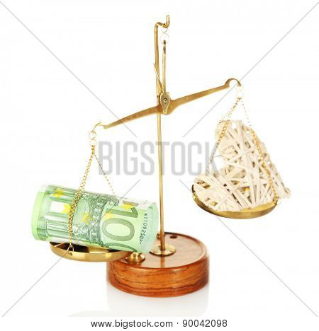 Money and heart in balance scales