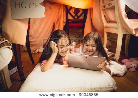 Happy Girls Using Digital Tablet In House Made Of Blankets