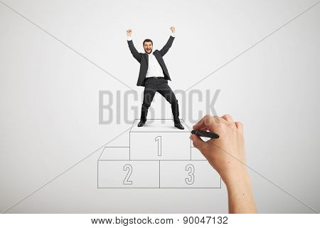 big hand drawing winners podium. happy laughing businessman in formal wear standing on sport winners podium and raising his hands up over light grey background