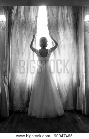 Rear View Of Elegant Bride Posing At Big Window In Bedroom