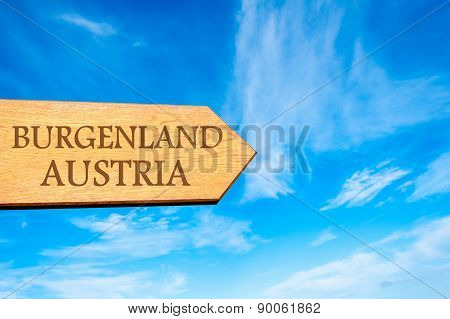 Wooden arrow sign pointing destination BURGENLAND AUSTRIA against clear blue sky with copy space available. Travel destination conceptual image poster