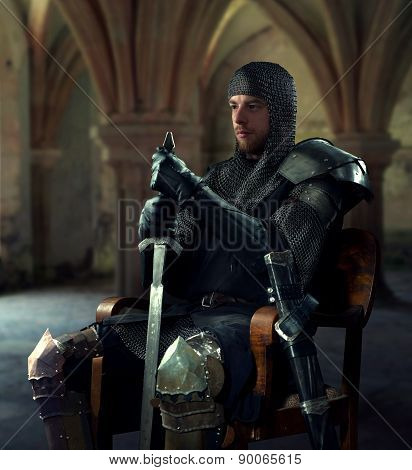 Ancient knight in metal armor sitting on a wooden chair in a palace poster