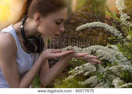 woman smelline flowers