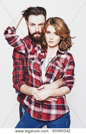 life style, happiness and people concept: Hipster couple. Beautiful young loving couple pposing  while standing against white  background.