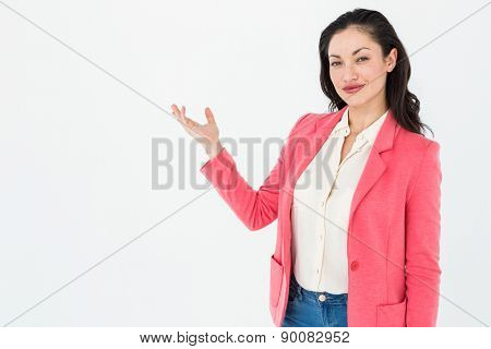 Elegant brunette presenting with her hand on white background