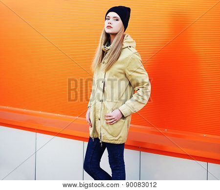 Outdoor Fashion Portrait Of Stylish Hipster Girl Standing In The City Against A Colorful Wall
