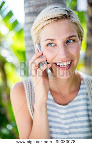Pretty blonde woman calling on the phone in the park