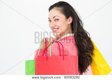 Smiling brunette holding shopping bags on white background