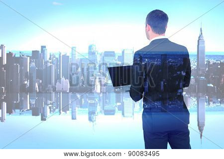 Businessman looking up holding laptop against mirror image of city skyline