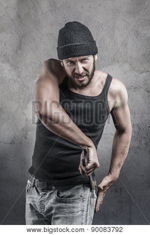 Thug preparing to use a wrench as a weapon pulling it out of the pocket of his jeans as he watches the camera with a dangerous angry expression over a textured grey background poster