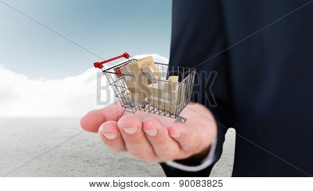 Mid section of a businessman with hands out against cloudy sky background