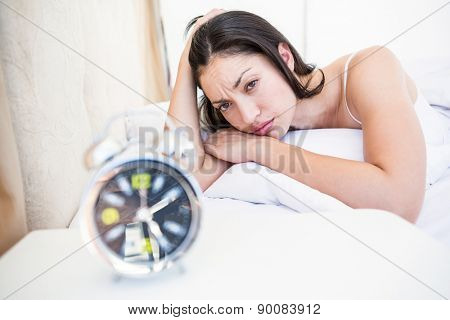 Pretty brunette watching alarm clock on bed at home