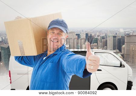 Happy delivery man holding cardboard box against new york