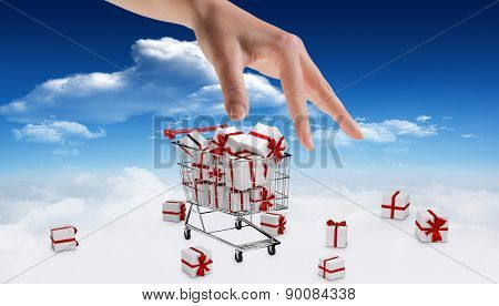 Hand showing against bright blue sky with clouds