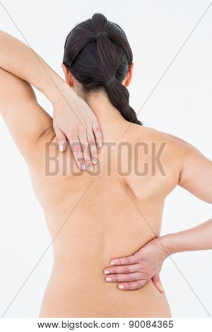 Brunette touching her painful back on white background