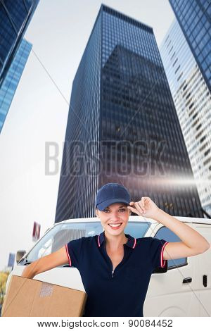 Happy delivery woman holding cardboard box against skyscraper in city