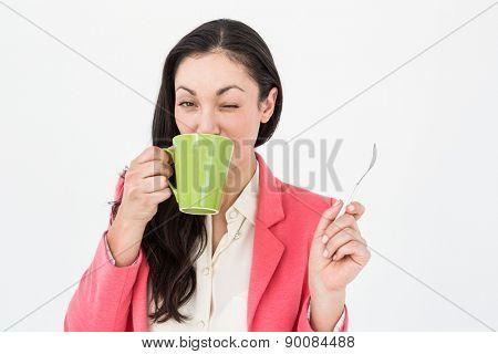 Smiling brunette drinking hot beverage on white background