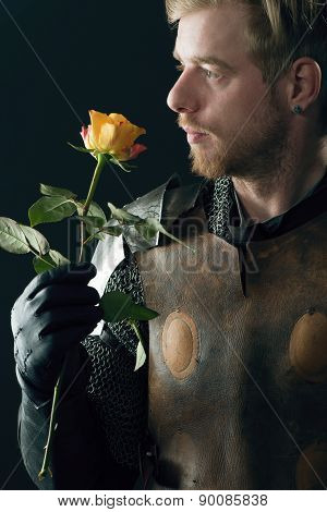 Close up portrait of ancient knight with yellow rose