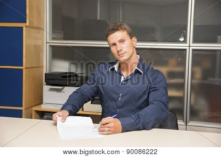 Young man doing paperwork at office desk, writing on a document