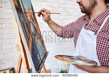 Young artist painting with oilpaints on canvas