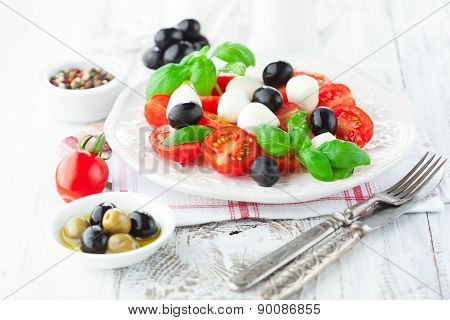Tomatoes And Mozzarella With Basil Leaves