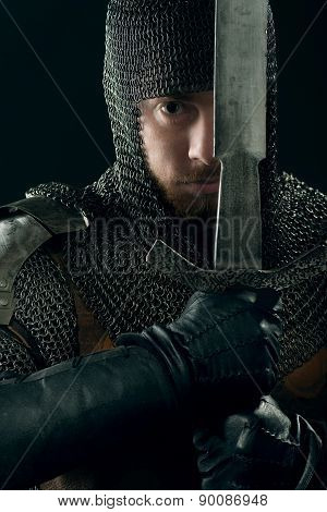 Ancient knight in metal armor with sword in hands