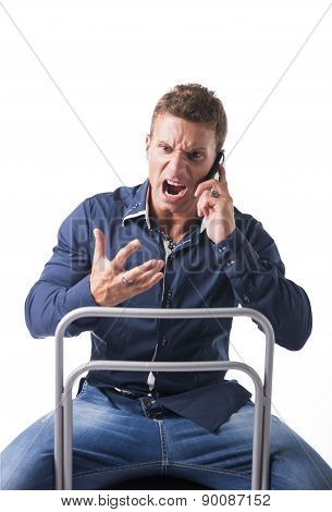 Young man sitting and screaming during phone conversation