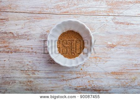 Grated Nutmeg In A Bowl On Wooden Table