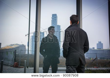 Stylish trendy young man standing outdoor in front of office window