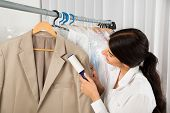 Female Cleaner In Laundry Shop Removing Lint From Clothes With Adhesive Roller poster
