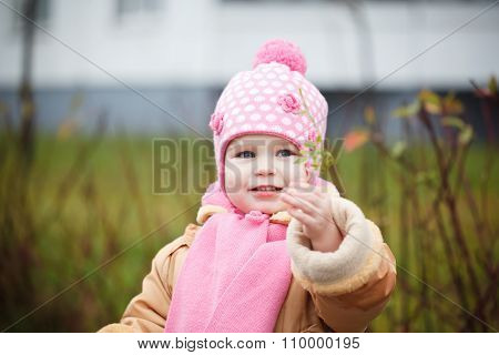 Happy Baby Girl In A Pink Hat And Scarf Laughs In Autumn