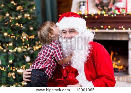 Santa Claus and little child boy. Kid telling his Christmas wish in Santa Claus near the Christmas o