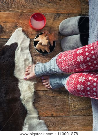 Close up of woman wearing christmas print pajamas with hot milk and gingerbread. Winter xmas concept.