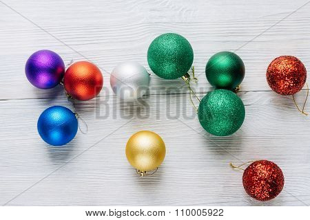 Colored Christmas Decorations Scattered On A White Wooden Table
