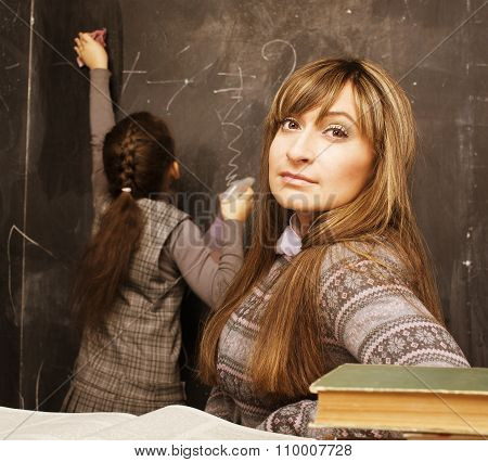 teacher with pupil in classroom at blackboard writting, girl at school