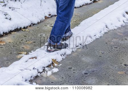 man walking along a narrow path perilous winter at wet weather