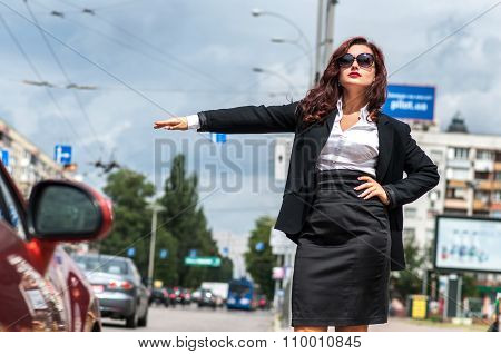 Pretty girl in the street stopping transport with thumb up